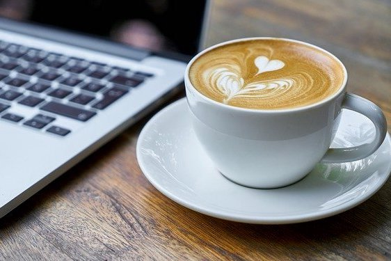 A latte is shown near a laptop