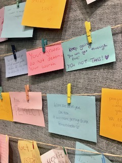 Notes of encouragement are pinned to a library wall