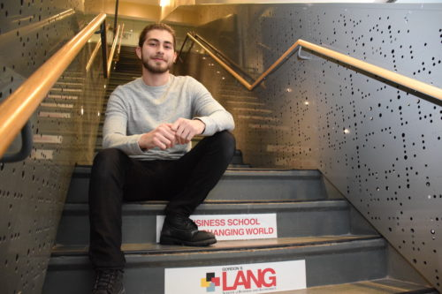 Bartu Suer sits on the stairs at the Gordon S. Lang School of Business and Economics