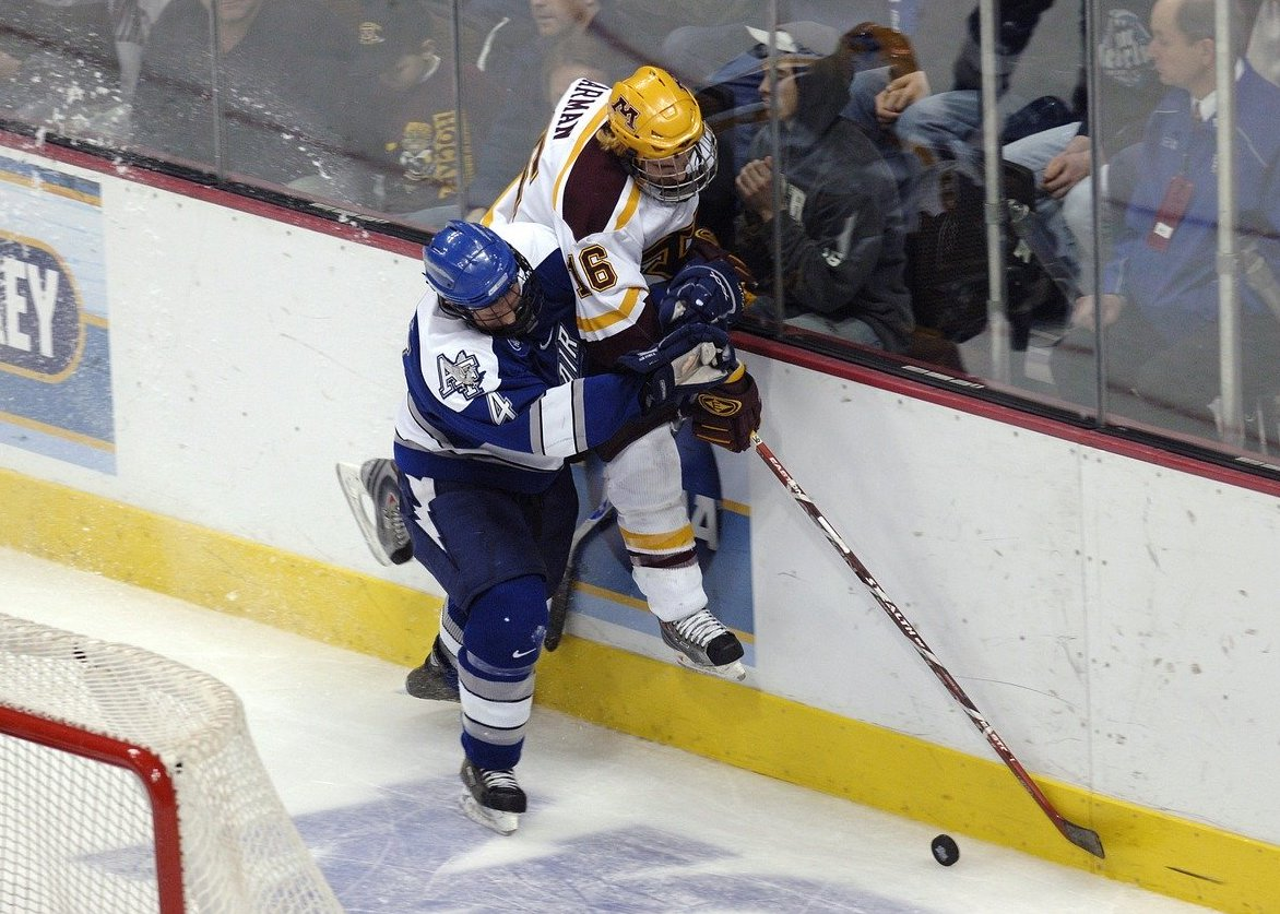 A hockey player forces another against the boards
