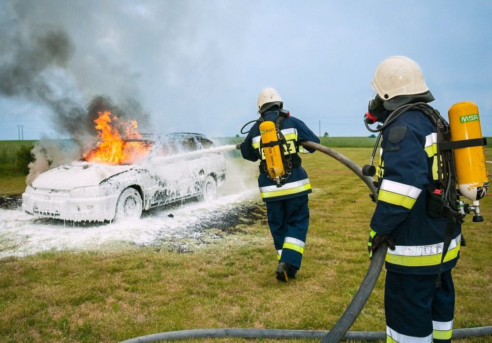 Two firefighters use foam to extinguish a car fire.