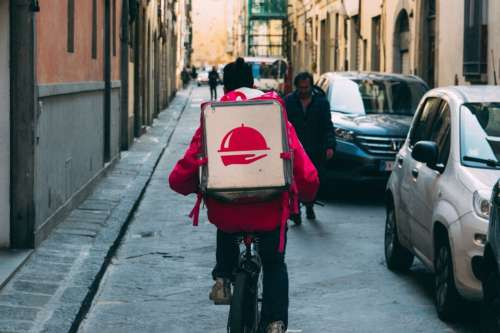 A Foodora bike courier in a narrow street