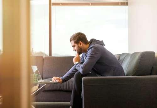 Man sitting on sofa works on laptop