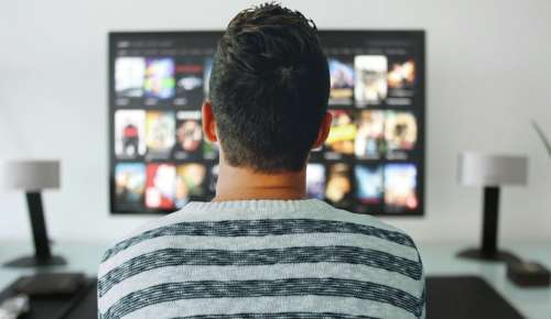 The back of a man watching TV