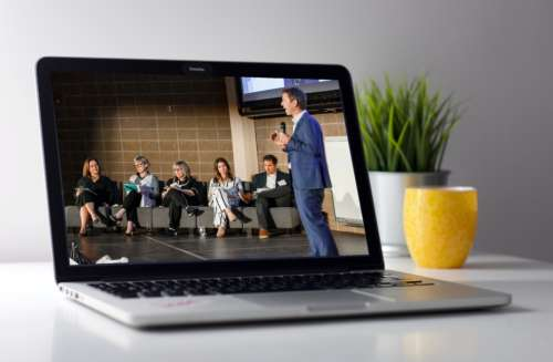 A laptop showing a speaker before a panel of judges on screen