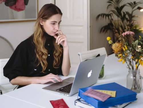 A young woman works at a laptop
