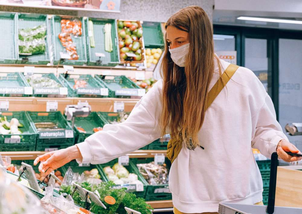 A woman wearing a mask shops for produce in a grocery store