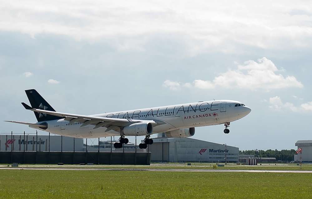 An Air Canada flight begins takeoff at an airport
