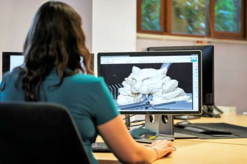 a woman sits at a computer doing 3D modelling