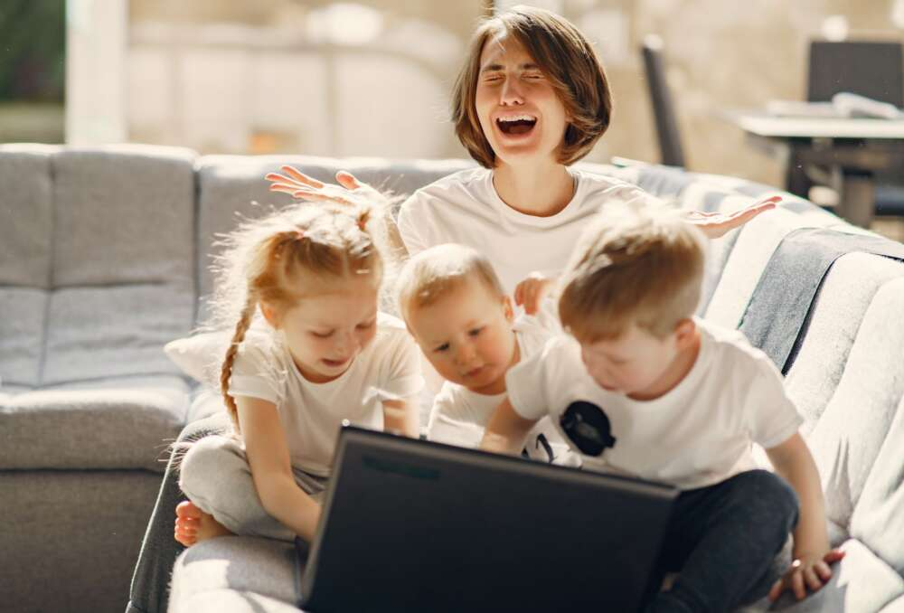 A mother is frustrated as 3 small children use her laptop.