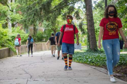 U of G students wearing masks walk along campus paths