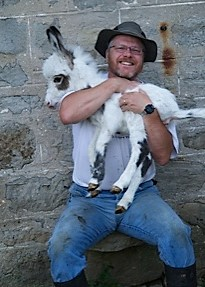 Prof. Andy Robinson holds one of his miniature donkeys