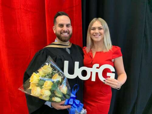 A graduate holds flowers alongside a woman holding a UofG sign