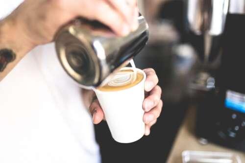 A barista pours foam onto a latte