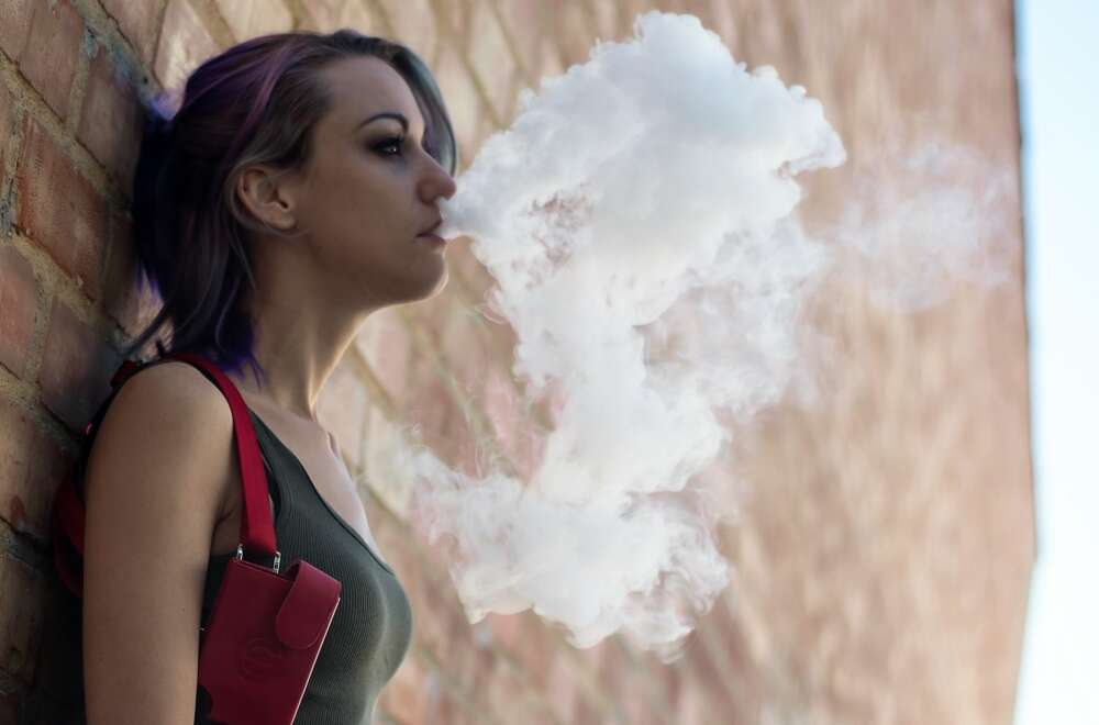A teen girl blows out vape steam