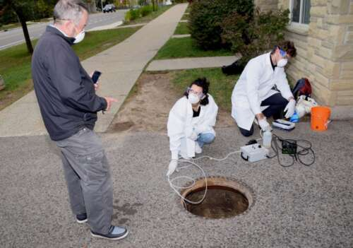 Engineering professor Ed McBean takes samples of wastewater at the University's East Residence with student research assistants Jonathan Evans and Melissa Novacefski.