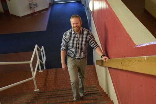 Smiling man walking up stairs