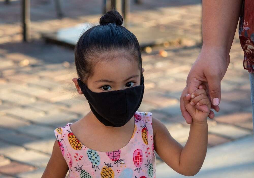 A preschooler wears a black surgical mask