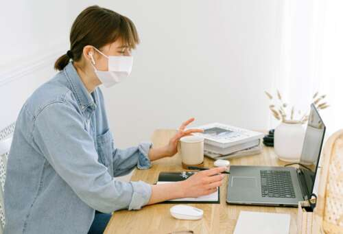 A woman in a mask works at a laptop