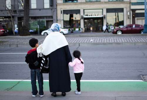 A mother stands with 2 children waiting to cross a street