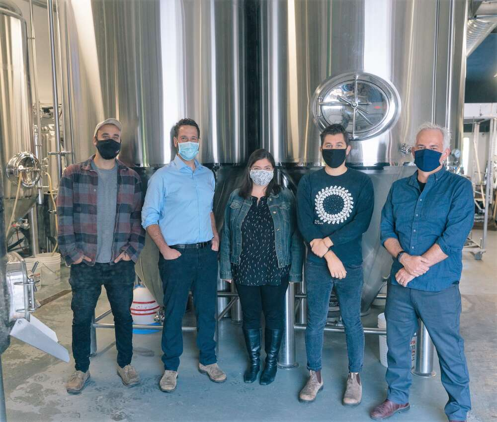 Five people stand in front of brewing kettles at Royal City Brewing
