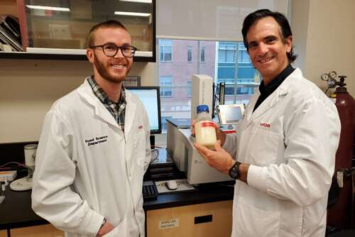 Prof. Alejandro Marangoni and PhD student Reed Nicholson wear lab coats and hold a bottle of liquid fat