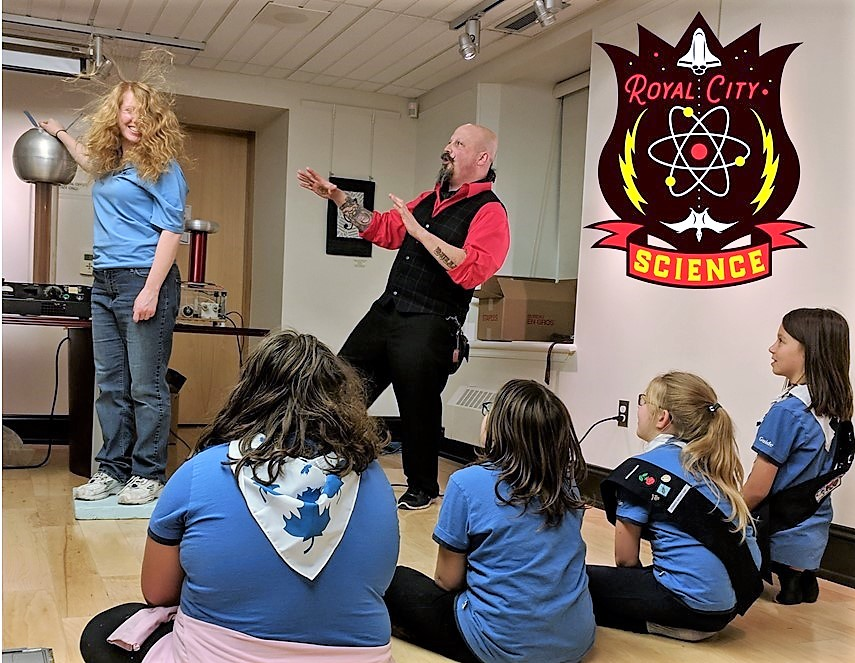 Girl Guides sit before Orbax as he demonstrated a plasma ball.