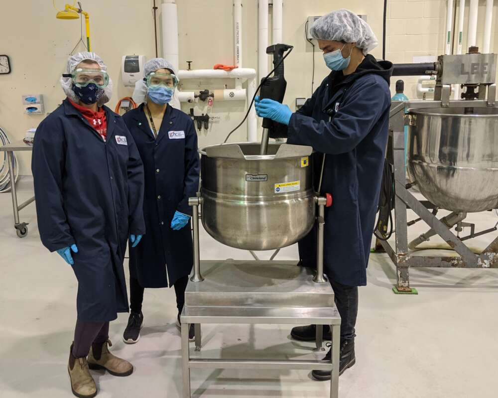 Three people wear face masks, hair nets and lab boats while working with large kitchen equipment