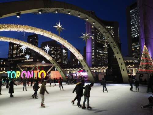 Outdoor rink with large arches and city buildings