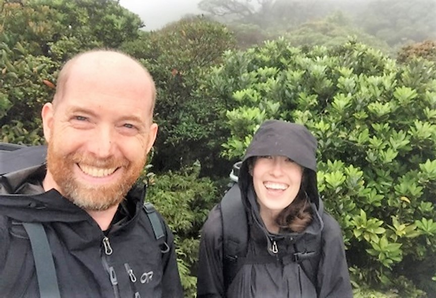 Prof. Alex Smith and Sarah Dolson stand in rainforest in rain coats