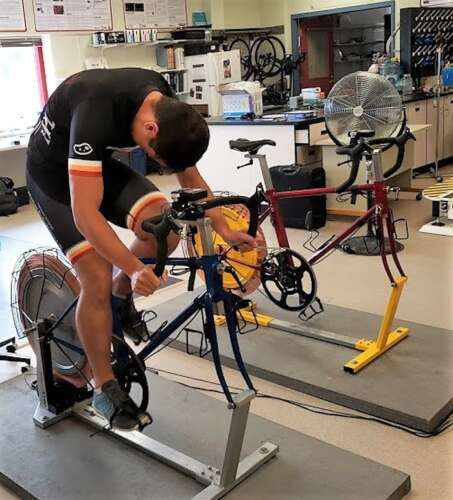 A man rides a cycling ergometer in a lab.
