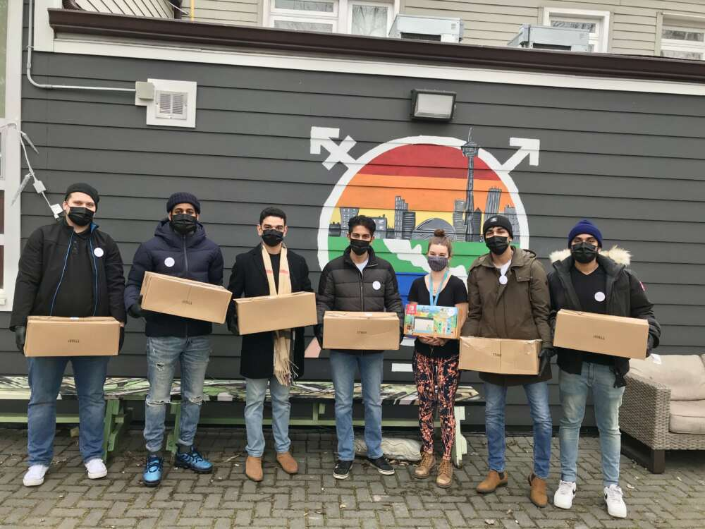 Seven Hygiene for the Homeless volunteers stand in a row holding carboard boxes