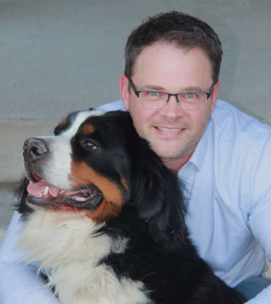Photo shows Dr. Jason Coe sitting with his dog Harley