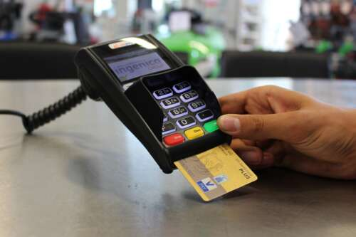 A hand inserts a credit card into a payment terminal