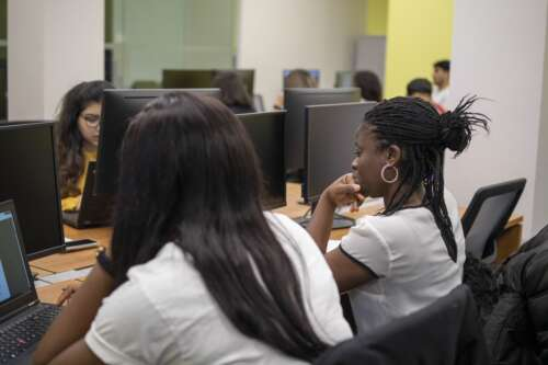 two students facing computer screens in a classroom