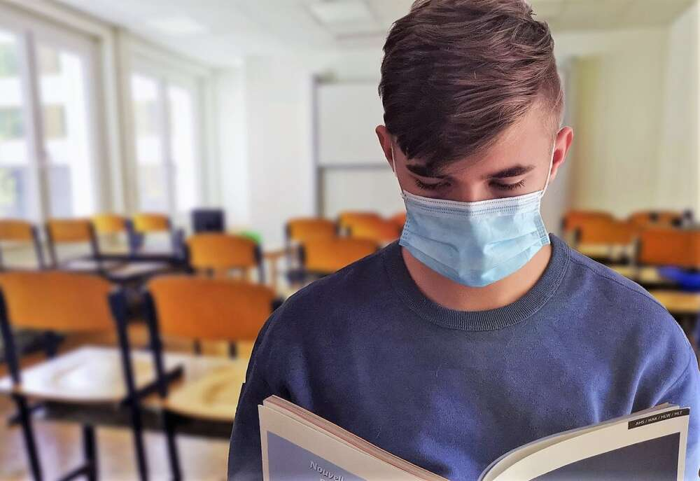 A boy wearing a mask looks at a book in a classroom