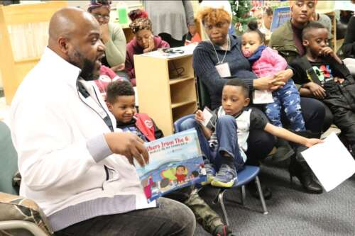 Black man reads from children's book to room full of children and mothers.