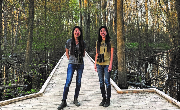 Kitty and Jenny Lin stand on a boardwalk at the U of G Arboretum
