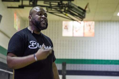 """Black man in a """"Blessed"""" t-shirt speaks inside a school gymnasium"""