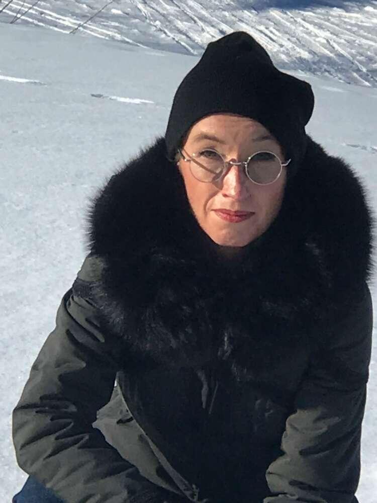 Sharon Edmunds crouches amid snow