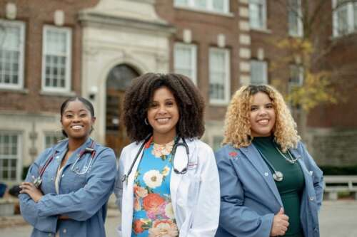 Three Black women in front of OVC building, each wearing a stethoscope