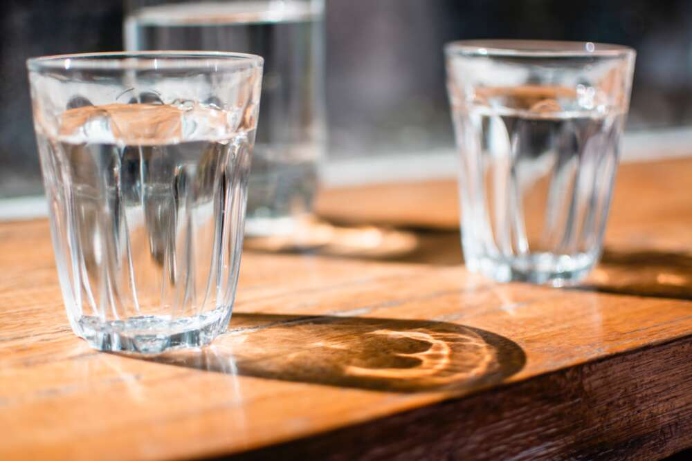 Three full water glasses sit on a table