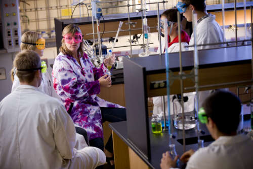 U of G students in the lab, wearing goggles, with test tubes and piping around them