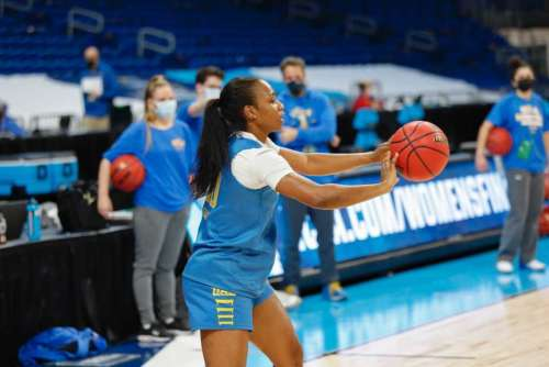 A player with the UCLA Bruins Women's basketball team. holds a ball and prepares to take a shot.