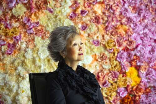 Adrienne Clarkson with pink, orange and yellow floral pattern in the background
