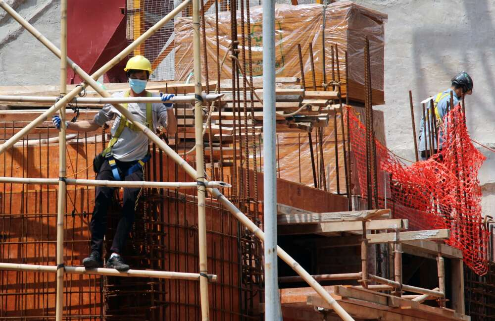 Two construction workers wearing face masks stand on scaffolding at a construction site