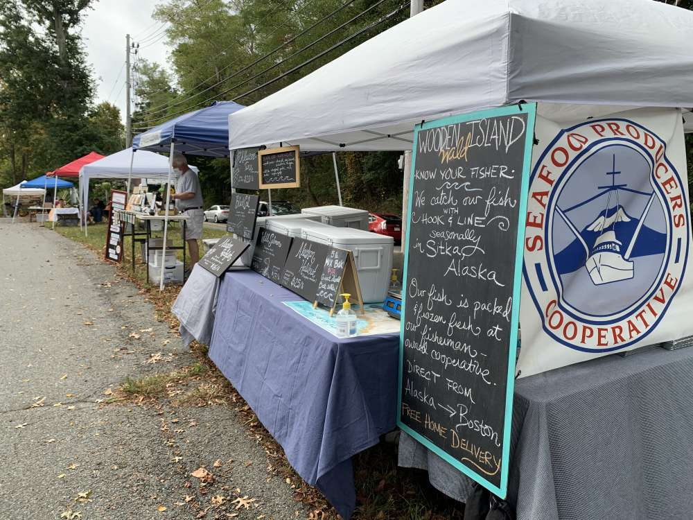 An outdoor farmers' market. The sign on the stall reads Seafood Producers Cooperative