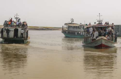 lartge boats on murkey brown water filled with people migrating because of floods
