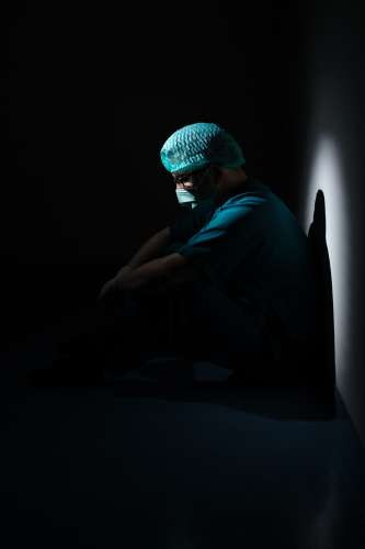 Masked health care worker in a dark setting