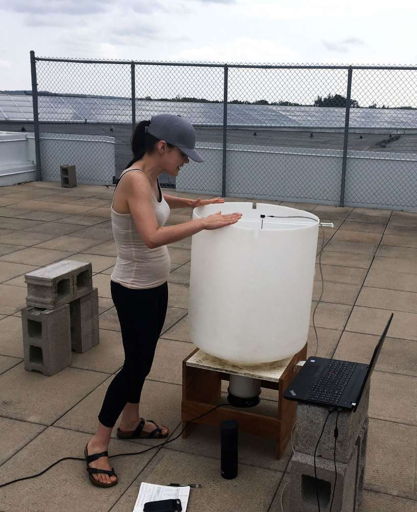 Alanna Wilcox stands on a rooftop and looks inside a large white plastic bin